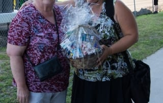 Woman holding a gift basket and posing with an elderly woman