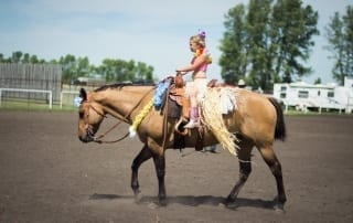 Colourfully dressed girl riding a horse